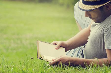 Photo pour Man reading a book on the grass - image libre de droit