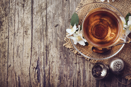 Photo for Cup of tea and jasmine flower on rustic wooden table, Top view. - Royalty Free Image