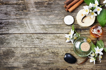 Photo pour Top view of spa products with copyspace. Essential oils with jasmine, cinnamon and vanilla on grunge rustic wooden table. - image libre de droit