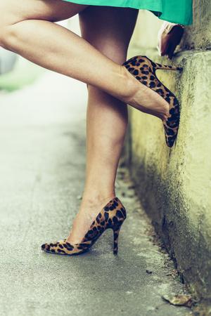 Foto de Sexy female legs closeup. Woman on the street in leopard pattern print high heeled shoes. - Imagen libre de derechos