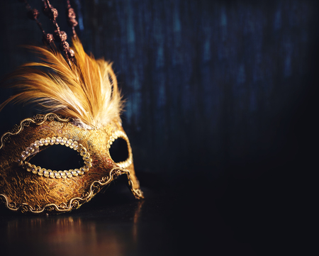 Photo pour Golden venetian ball mask over dark background with copyspace. Masquerade party or holiday event celebration concept. - image libre de droit