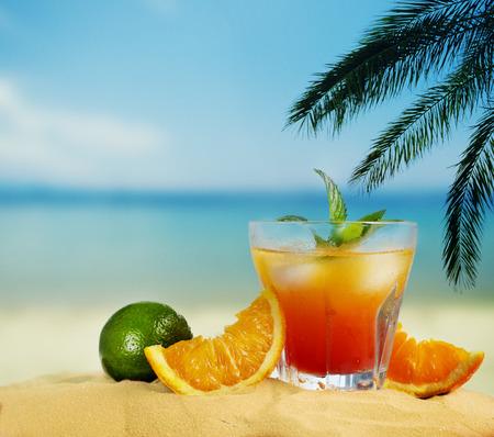 Foto de Orange cocktail and citrus fruit on tropical sandy beach. Summer holiday and beach party design. - Imagen libre de derechos