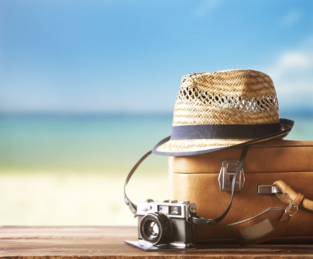 Foto de Vintage suitcase, hipster hat, photo camera and passport on wooden deck. Tropical sea and sandy beach a in background. Summer holiday traveling design concept. - Imagen libre de derechos