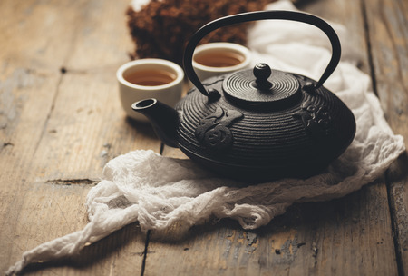 Photo pour Still life with traditional asian herbal tea prepared in vintage cast iron teapot with organic dry herbs on rustic wooden table. Retro filter. - image libre de droit