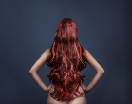 Photo pour Woman with perfect curly dyed hairstyle from behind. Fashion portrait of red head woman from the back over dark background. Perfect long red hair. - image libre de droit