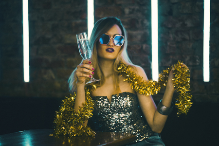 Photo pour Young happy woman celebrating new year eve drinking champagne. Night lights and confetti. Lady clubber in nightclub having fun. Hipster girl at celebration luxury party. - image libre de droit