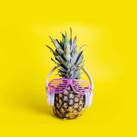 Foto de Fashionable  trendy pineapple fruit with headphones and sun glasses listen to the music over bright pastel yellow - Imagen libre de derechos