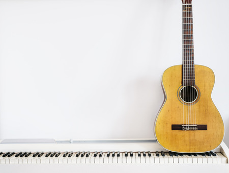 Foto de Acoustic guitar on piano keyboard in front of white wall. - Imagen libre de derechos