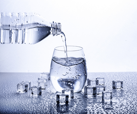 Foto de Pouring fresh drinking mineral water from plastic bottle. Glass filled with water over white background. - Imagen libre de derechos