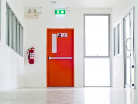Photo pour Building Emergency Exit with Exit Sign and Fire Extinguisher. - image libre de droit