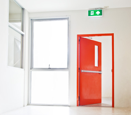 Photo pour Building Emergency Exit with Exit Sign, red door opening to white - image libre de droit