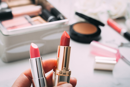 Photo for Woman's hand holds two lipsticks. Beauty products blurred background. Copy spase. - Royalty Free Image
