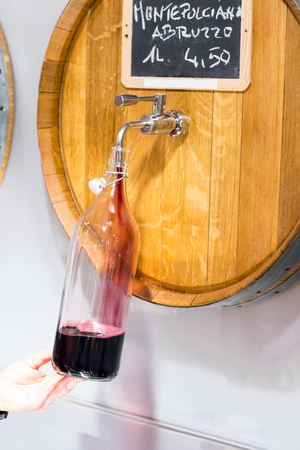 Photo for A man in a bid winery pouring wine from barrel in winebottle. One liter of wine. - Royalty Free Image
