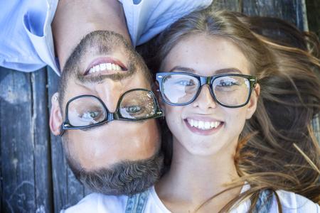 Photo pour portrait of young couple lying on wooden bench - image libre de droit