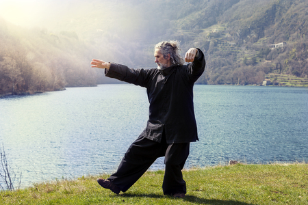 Foto de mature man practicing Tai Chi discipline outdoors in a lake park on a winter day - Imagen libre de derechos