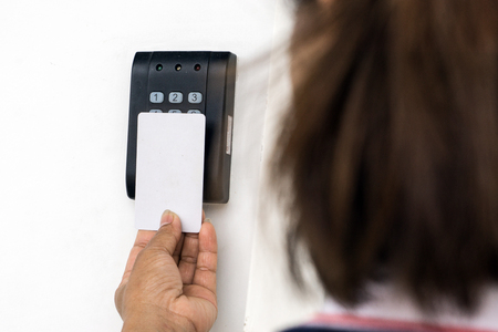 Foto de Door access control - young woman holding a key card to lock and unlock door., Keycard touch the security system to access the door - Imagen libre de derechos