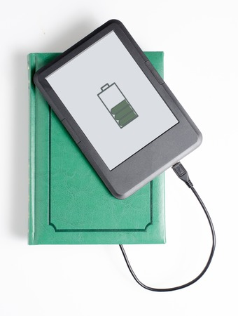 Foto de E-book and book connected with cable. White background. Vertical photo - Imagen libre de derechos