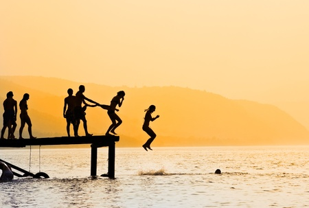 Silhouettes of kids who jump off dock on the lake at sunset.