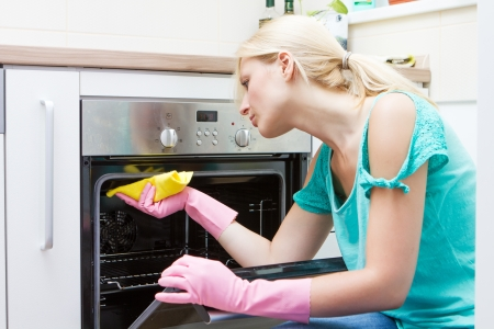 Photo pour Young woman cleaning oven in the kitchen. - image libre de droit