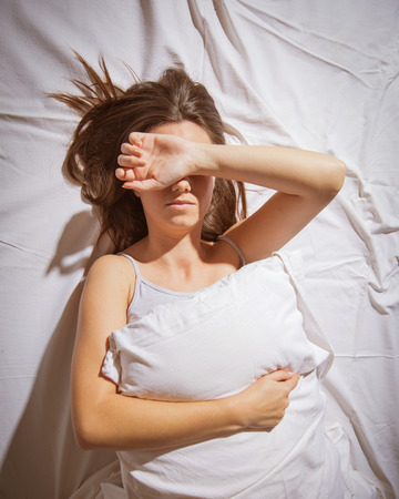 Foto de Young woman with insomnia cover her face with hand in bed. - Imagen libre de derechos