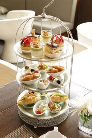 Photo pour Afternoon tea served with an assortment of cakes - image libre de droit