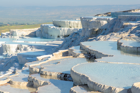 The enchanting pools of Pamukkale in Turkey. Pamukkale contains hot springs and travertines, terraces of carbonate minerals left by the flowing water.