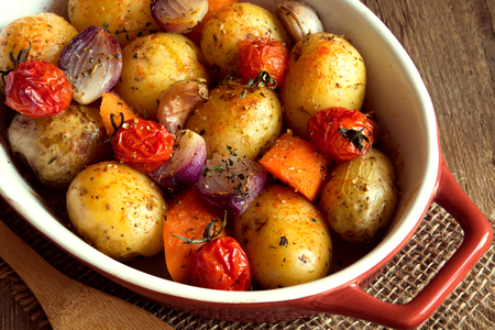 Photo pour Rustic oven baked vegetables with spices and herbs in baking dish close up, vegetarian organic autumn meal - image libre de droit