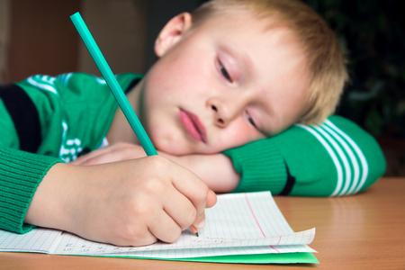 Foto de Tired boring boy doing his difficult school homework - Imagen libre de derechos