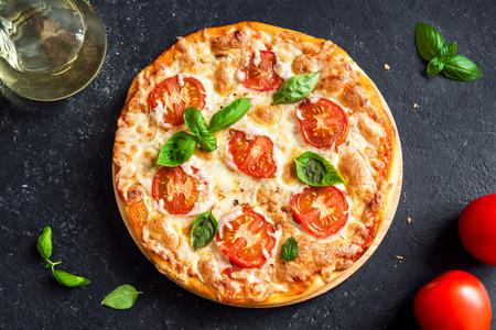 Photo for Pizza Margherita on black stone background. Homemade Pizza Margarita with Tomatoes, Basil and Mozzarella Cheese. - Royalty Free Image