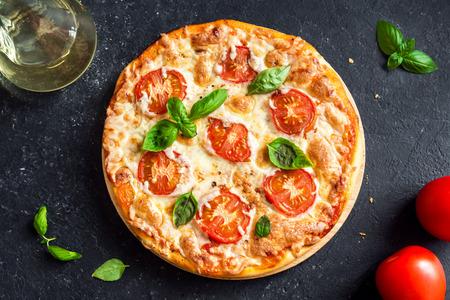 Foto de Pizza Margherita on black stone background. Homemade Pizza Margarita with Tomatoes, Basil and Mozzarella Cheese. - Imagen libre de derechos