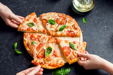Foto de People Hands Taking Slices Of Pizza Margherita. Pizza Margarita and  Hands close up over black background. - Imagen libre de derechos