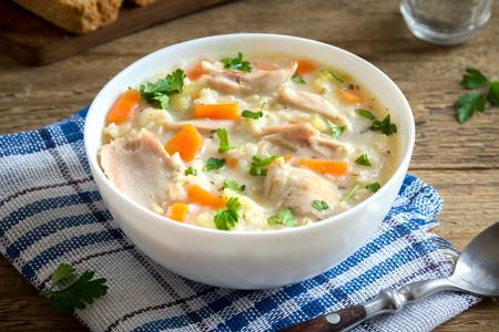 Foto de Chicken and Wild Rice Soup. Homemade fresh creamy soup with chicken, vegetables and wild rice in white bowl close up. - Imagen libre de derechos