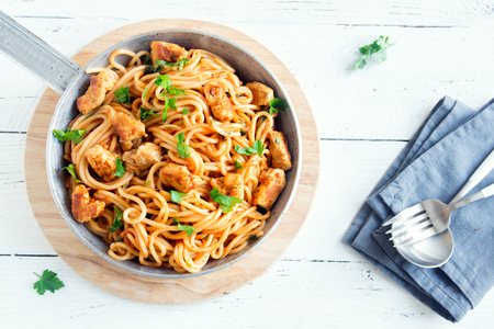 Photo for Spaghetti pasta in tomato sauce with chicken,  parsley in pan. Chicken spaghetti pasta over white wooden background with copy space, italian food. - Royalty Free Image