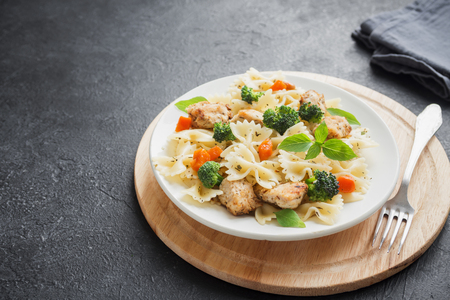 Photo for Farfalle pasta with chicken and vegetables. Pasta salad on black background, copy space. - Royalty Free Image
