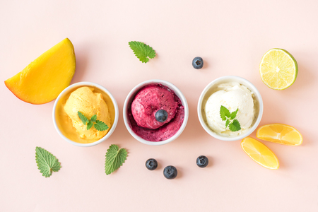 Photo for Three various fruit and berries ice creams on pink background, copy space. Frozen yogurt or ice cream with lemon, mango, blueberries - healthy summer dessert. - Royalty Free Image