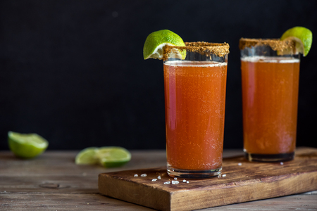 Photo for Michelada (Mexican Bloody Beer) with Spisy Rim and Tomato Juice served with Limes and Nacho Chips. Summer Alcohol Cocktail Michelada. - Royalty Free Image