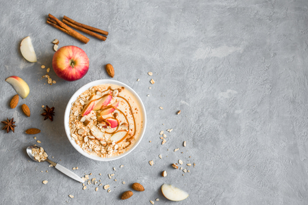 Photo for Apple Pie Smoothie Bowl. Breakfast smoothie bowl with apples, cinnamon, almond milk, oat granola, salted caramel and spices, top view, copy space. - Royalty Free Image