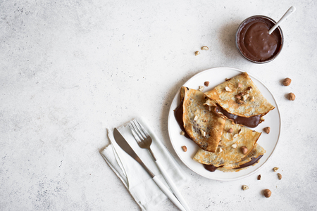 Photo for Crepes with chocolate and hazelnuts. Homemade thin crepes for breakfast or dessert on white, copy space. - Royalty Free Image