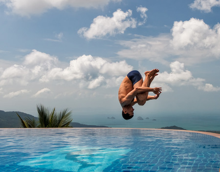 Photo pour Young athletic man jumps into the pool at the top of the mountain - image libre de droit