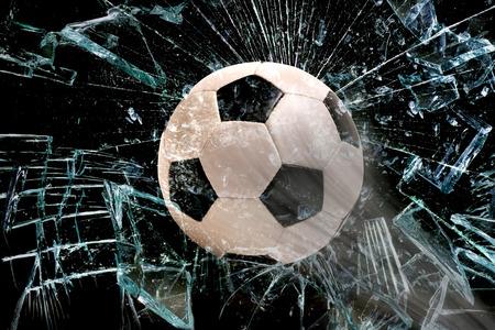 Photo pour Fast Soccer ball through broken glass. - image libre de droit