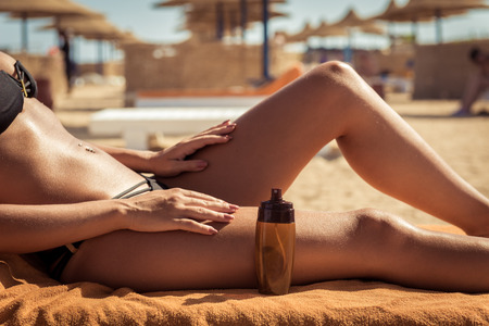 Foto de Sensuous slim woman applying suntan lotion oil to her body at the beach - Imagen libre de derechos