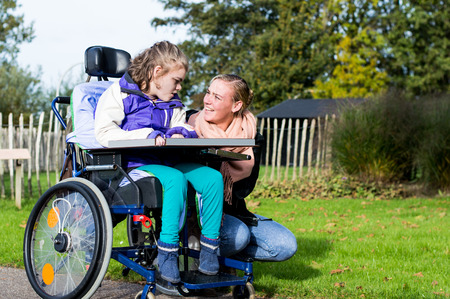 Foto de A disabled child in a wheelchair with care assistant - Imagen libre de derechos