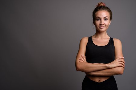 Photo for Young beautiful woman ready for gym against gray background - Royalty Free Image