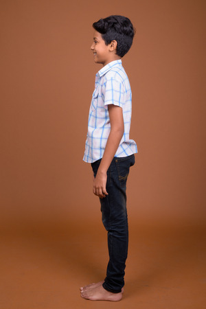 Photo pour Young Indian boy wearing checkered shirt against brown backgroun - image libre de droit