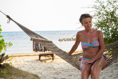 Foto de Mature beautiful tourist woman relaxing at the beach - Imagen libre de derechos