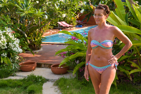 Foto de Mature beautiful tourist woman wearing bikini at the resort - Imagen libre de derechos