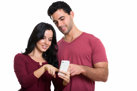 Photo pour Studio shot of young happy couple smiling while using one mobile - image libre de droit