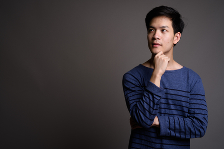 Foto de Young handsome Asian man thinking with hand on chin - Imagen libre de derechos