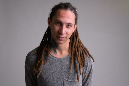 Photo for Portrait of happy young handsome man with dreadlocks smiling - Royalty Free Image