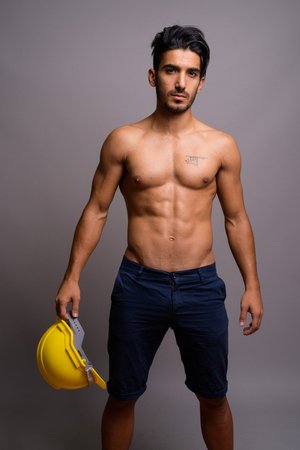 Photo for Young handsome Persian man construction worker shirtless against - Royalty Free Image